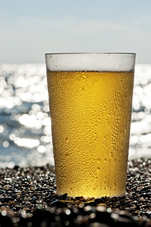 Plastic cup of beer standing on the sand by the sea. photo