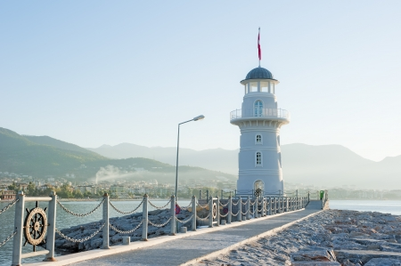 Landscape with a lighthouse in the harbor town of Alanya at dawn. Stock Photo