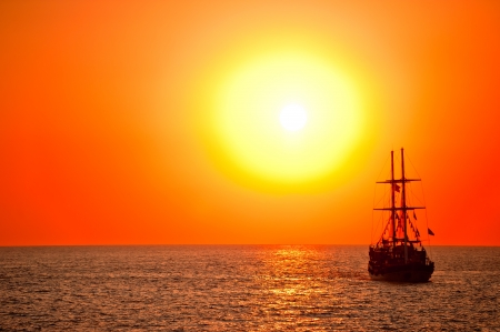 Tall ship drifting in the open sea at sunset  Stock Photo