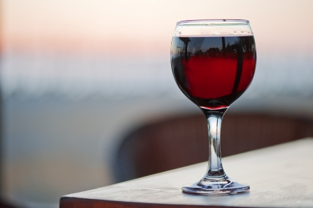 A glass of red wine at sunset.  photo