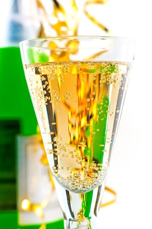 A glass of sparkling wine on the background of the bottle with a festive tinsel. Stock Photo - 16269522