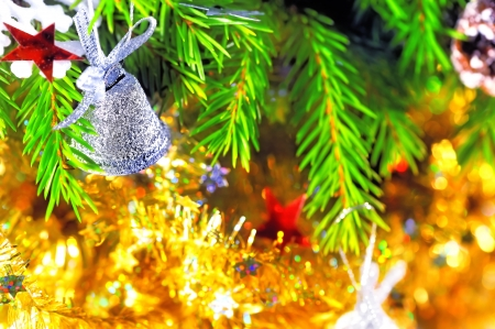 Silver bell hanging on the branch of a Christmas tree photo