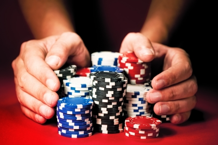 Man s hands move the winnings casino chips on red table