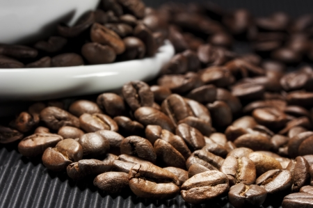 Coffee beans scattered on a black grooved photo