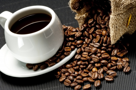 White cup of coffee and spilled coffee beans photo