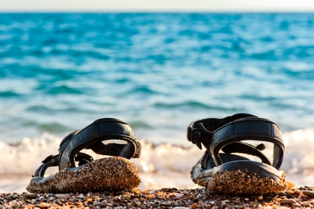 Beach shoes at the edge of the sea on the sandy beach