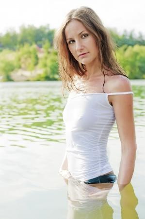 umida: Bella ragazza in maglietta bagnata sta cintola in acqua
