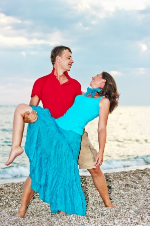 Young couple dancing on the sandy sea beach photo