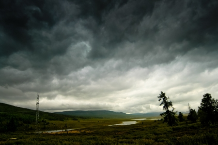 Black stormy sky in the rain in the mountains  Altai  Russia photo