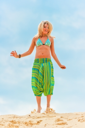 Young slim girl jumping in the sand   Stock Photo