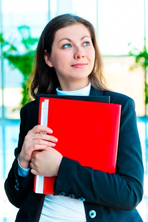 encouraged: Encouraged by a businesswoman holding a red folder with documents on background of office interior