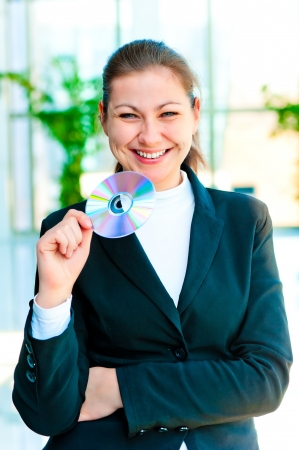 Young happy business woman holding compact disc photo