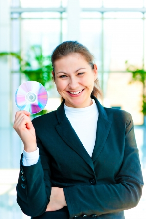 Happy brunette woman holding a CD on blurred background office photo