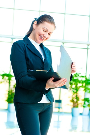 Young happy business woman with an open folder in hand photo