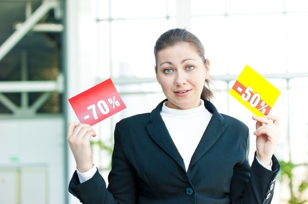 rebates: Brunette girl in confusion holds two tablets with discounts Stock Photo