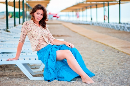 Beautiful young girl posing on a beach lounger photo