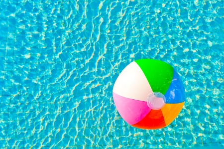 colorful beach ball floating in a pool Stock Photo