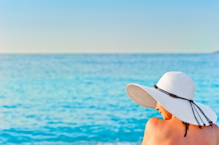 girl in white hat on the beach sunbathing photo