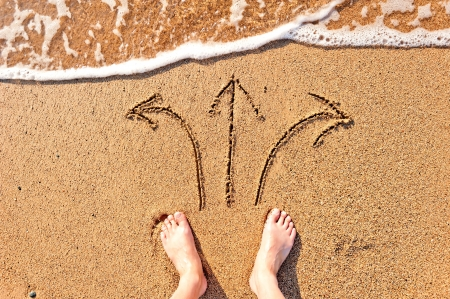 man bare feet in the sand and arrows