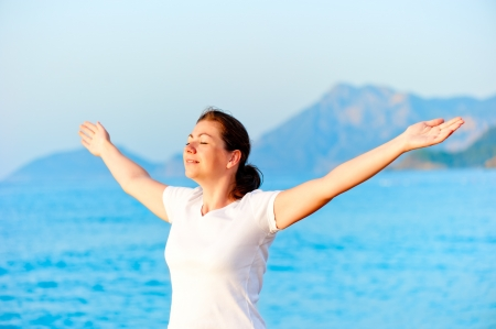 Woman with arms outstretched enjoying the sun by the sea photo