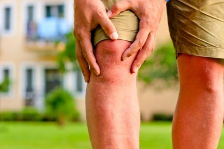 artrite: uomo mani della holding ginocchio dolorante