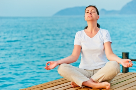 girl sitting on a pier in the lotus position