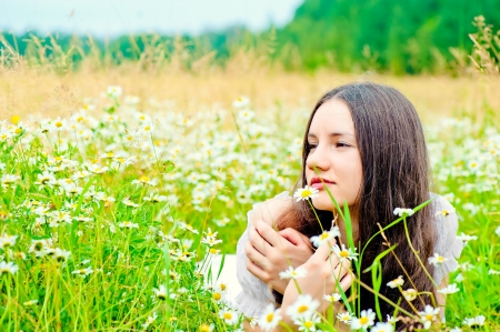 girl resting in a field of chamomile in a white dress photo