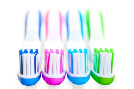 four new multi-colored toothbrushes are on a white background photo