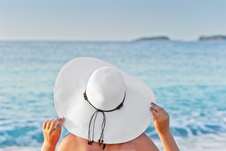 A woman sunbathing on a deck chair on the beach and holding hands hat photo