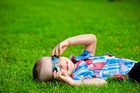 happy boy resting lying on green grass in sunglasses photo