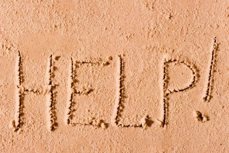 on the wet sand written the word Help! by the sea Stock Photo