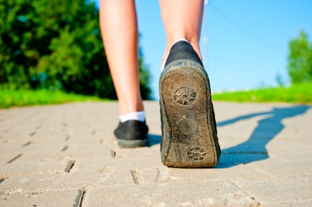 female legs in sneakers close up running down the road in the morning Stock Photo