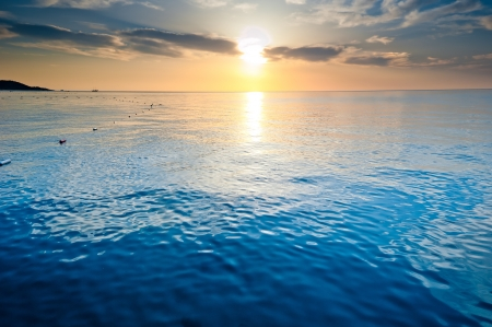sun lit: the calm sea of the rising sun lit the clouds Stock Photo