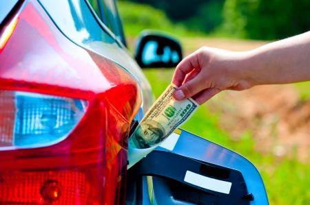 female hand puts the car into the gas tank one hundred dollars photo