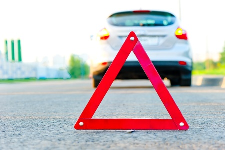 red warning triangle and a car with the emergency alarm