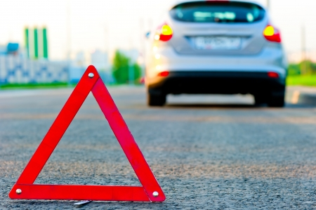 warning triangle on the road and the car moved down to the curb photo