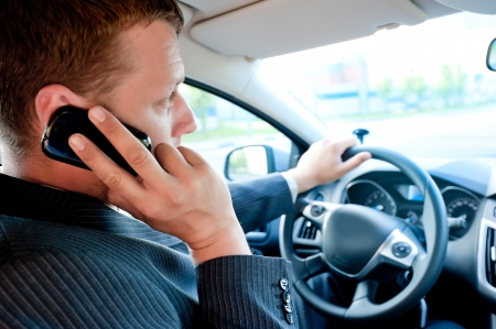 businessman talking: male businessman talking on a cell phone while driving