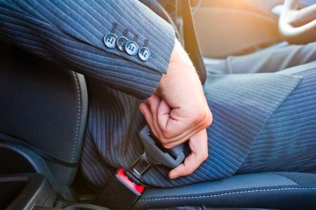 asiento coche: Conductor en traje de negocios se mantiene fuerte su asiento propio cinturón de seguridad del automóvil Foto de archivo