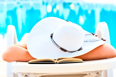 girl asleep in a lounge chair near the pool with a book photo