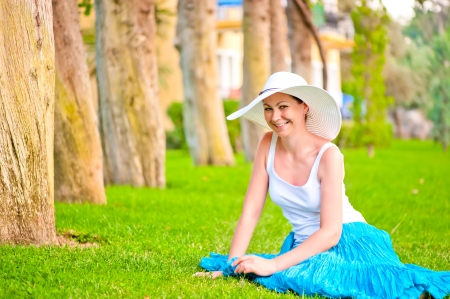 gaily: Girl resting on the lawn and laughs gaily