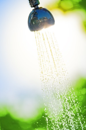 flowing water from a watering can shower in the sun