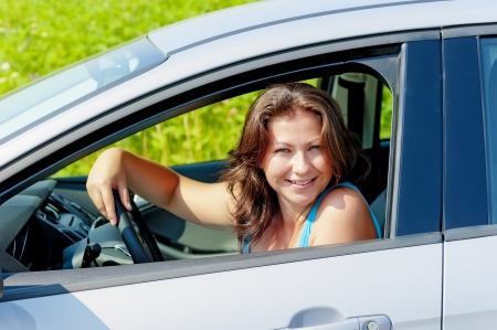Portrait of a cheerful woman driving a car photo