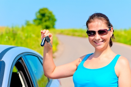 young woman proudly displays the keys to her new car photo