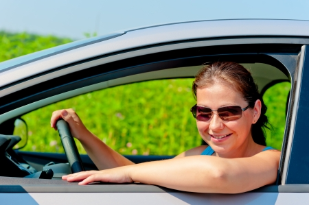 woman in sunglasses driving a modern car photo