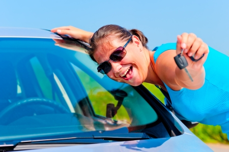 happy woman showing keys of her new car photo