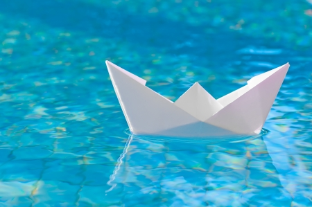 White paper boat floating in the water photo