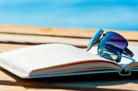 open book and sunglasses on the background of the sea Foto de archivo