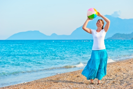 girl plays with a beach ball near the sea photo