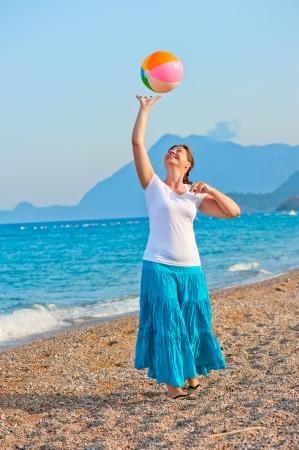 beautiful girl playing on the beach ball photo