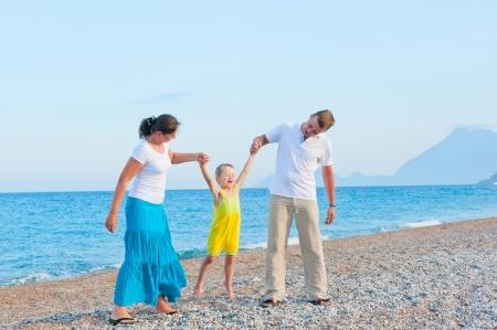 parents shake their little son on the beach photo